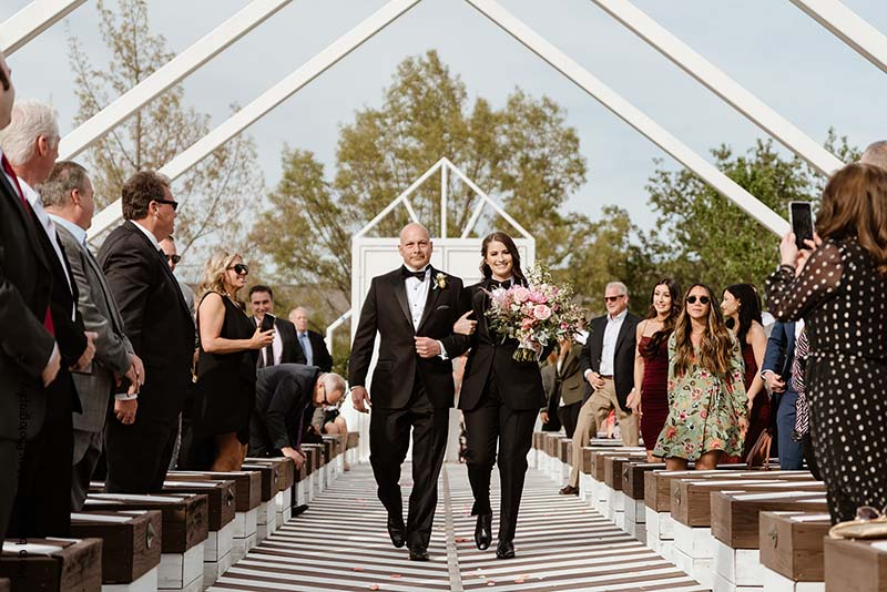 Father walks bride in black suit down aisle