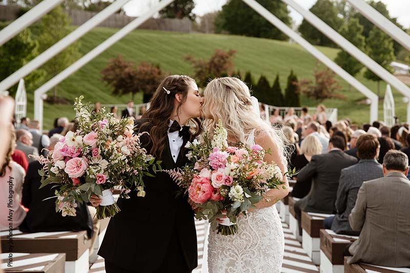 Brides kiss as they walk down aisle after ceremony