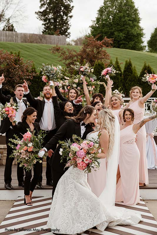 Brides kiss with wedding party celebrating behind