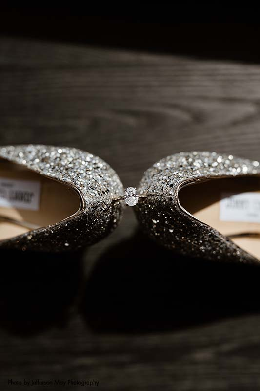 Oval diamond engagement ring sits between sparkly Jimmy Choo shoes