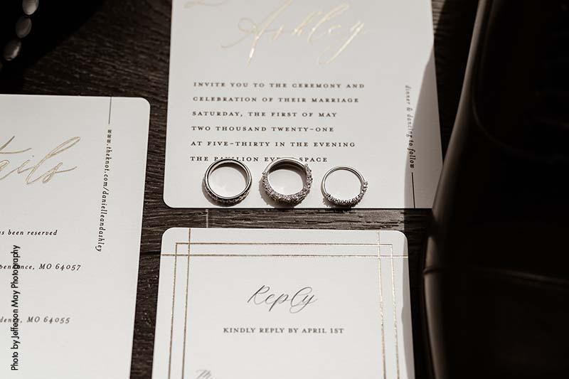 White gold wedding bands sit on wedding stationery