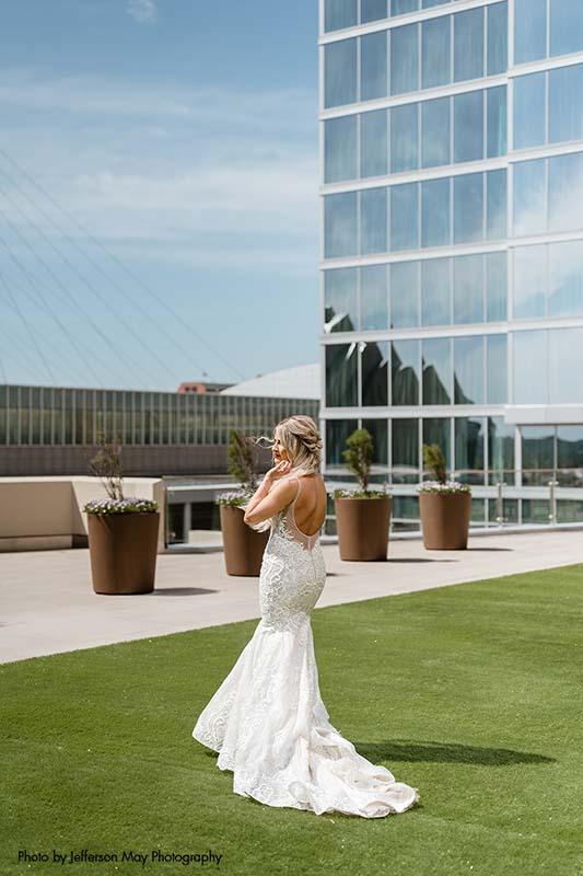 Bride in mermaid dress stands on rooftop in Kansas City