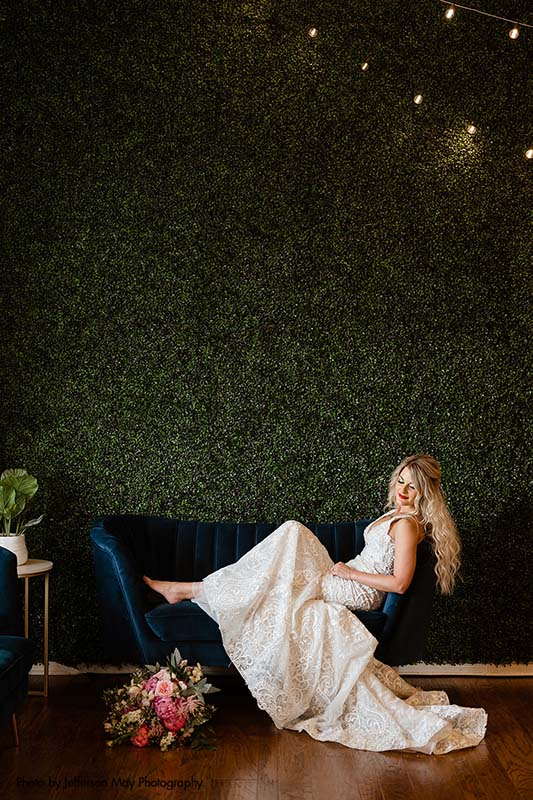 Bride sits on blue velvet couch