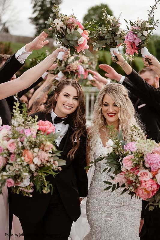 Brides walk through wedding party tunnel