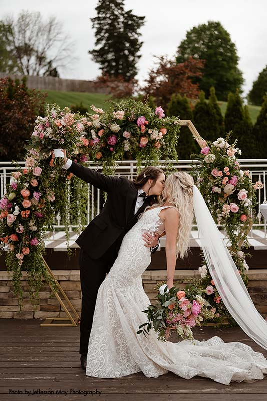 Hexagon wedding ceremony arch with greenery and pink and white flowers