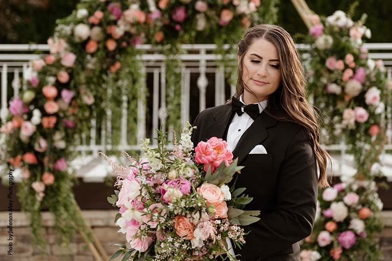 Bride in custom black tuxedo with large spring bouquet