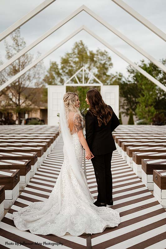 Bride in mermaid dress and bride in black tux at modern outdoor cermony