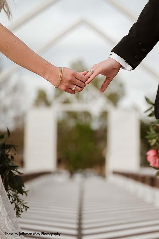 Brides hold hands at wedding ceremony