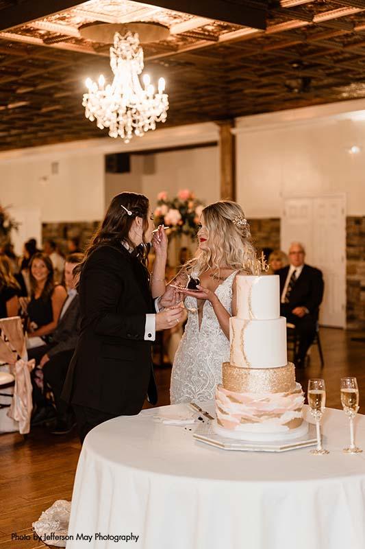 Brides cut cake at wedding