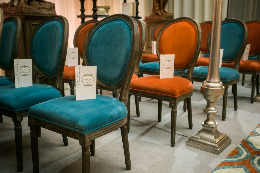 Velvet oval blue and orange wedding chairs at Unveiled Wedding Event in Minneapolis