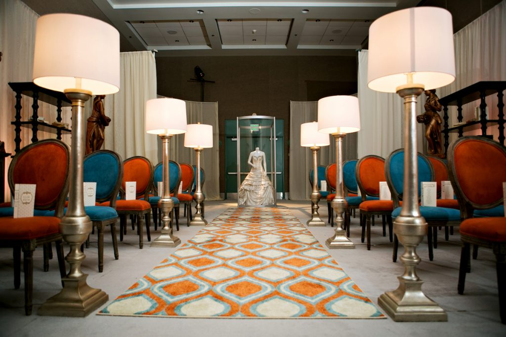 Vibrant wedding ceremony setup with orange geometric aisle runner