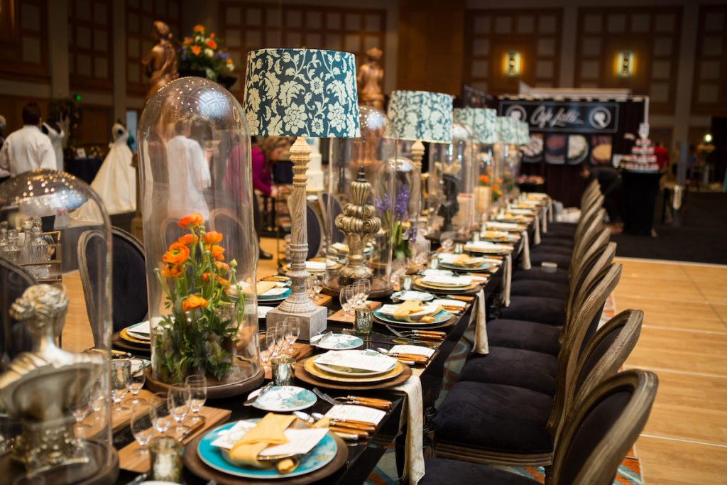 Long wedding community table with glass cloches and bright china
