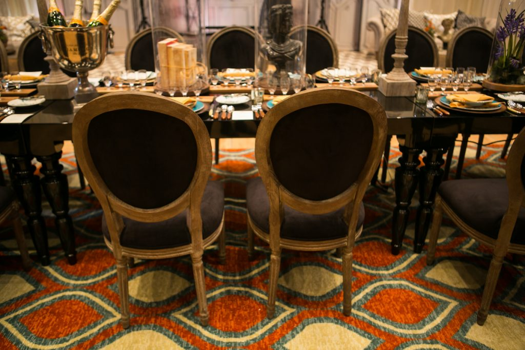 Velvet black wedding chairs on top of orange and blue geometric carpet