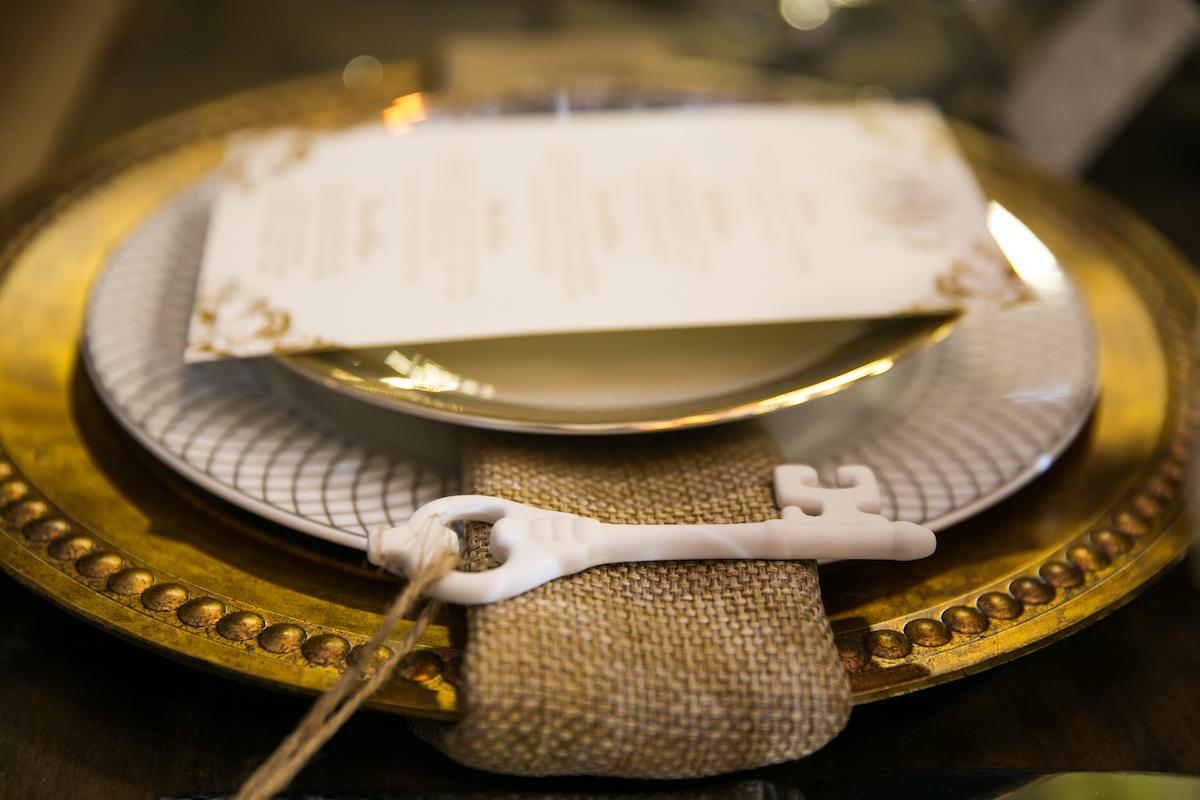Skeleton key sits on top of burlap napkin at wedding