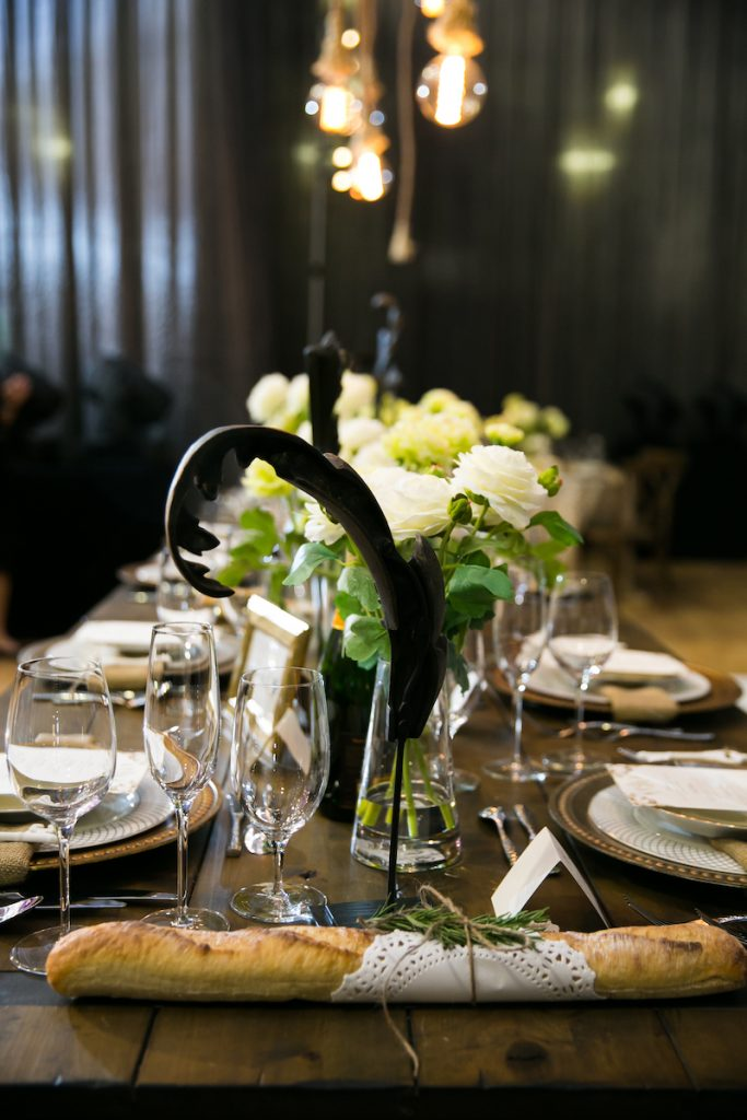Farm table at wedding with simple glass stemware and loose floral centerpieces