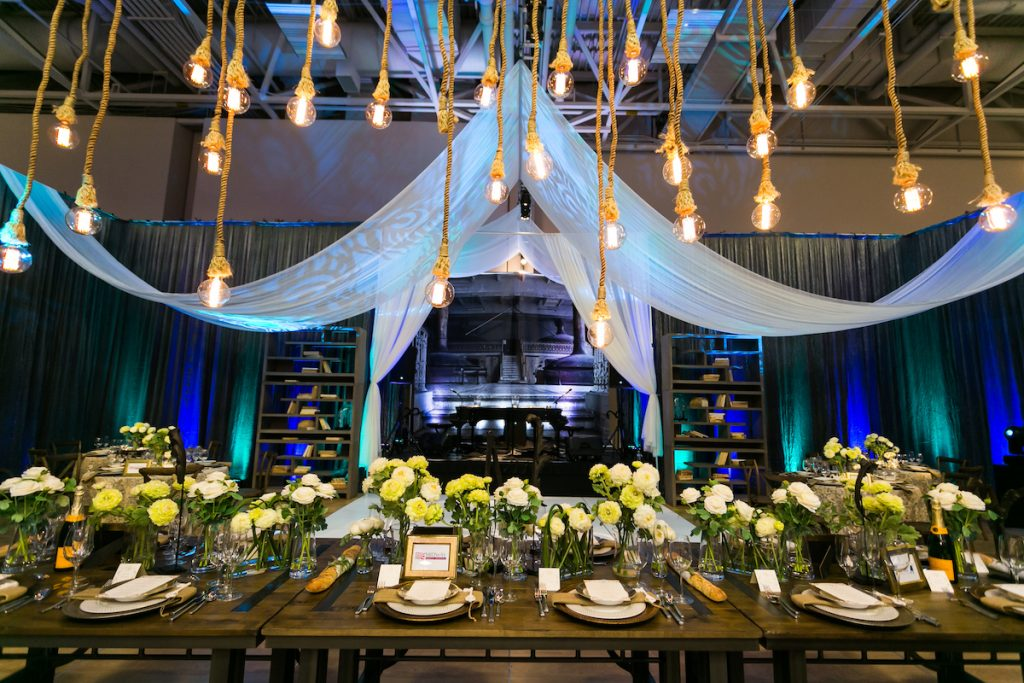 Pale blue linens hang from ceiling above wedding table