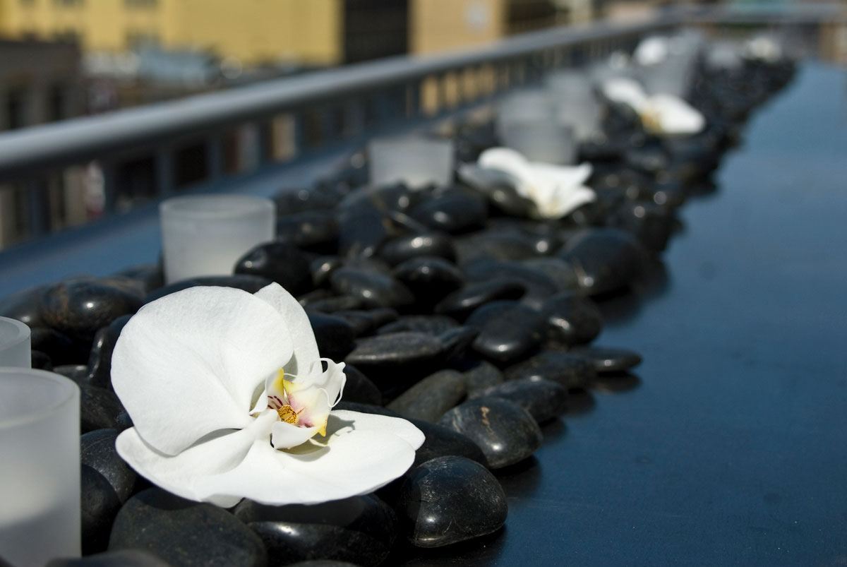 Black river stones with orchids and votives lay on head table at wedding