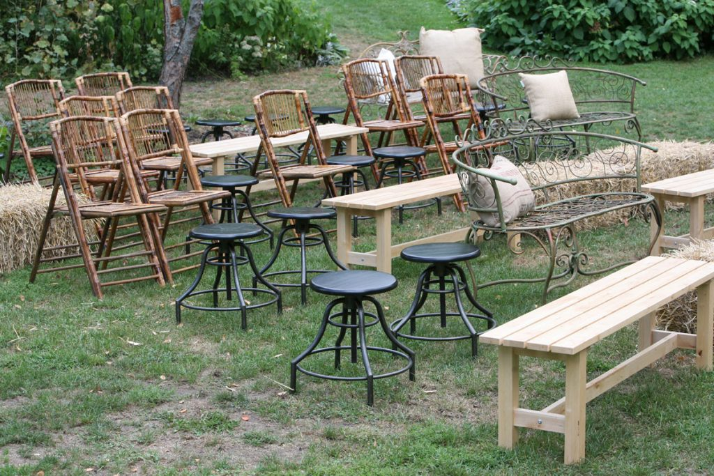Mixed ceremony seating with benches, wooden chairs, and black stools