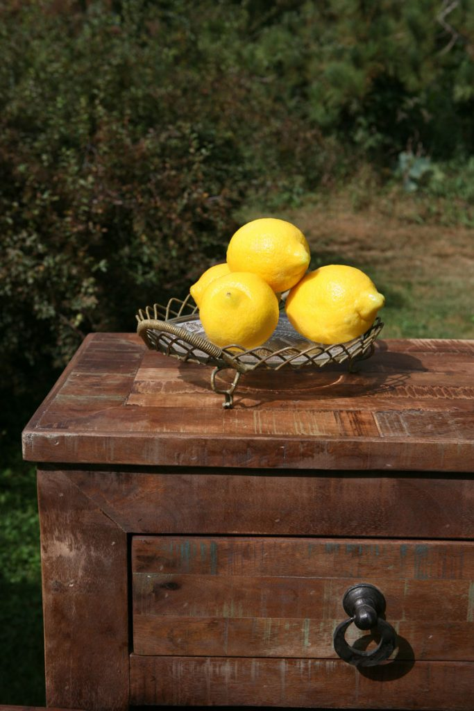 Lemons sit in basket on distressed table