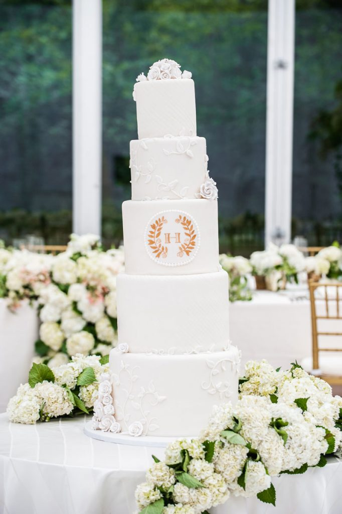 5-tier white wedding cake surrounded by greenery garland