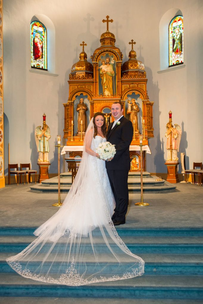 Bride and groom stand at the alter in a Catholic church