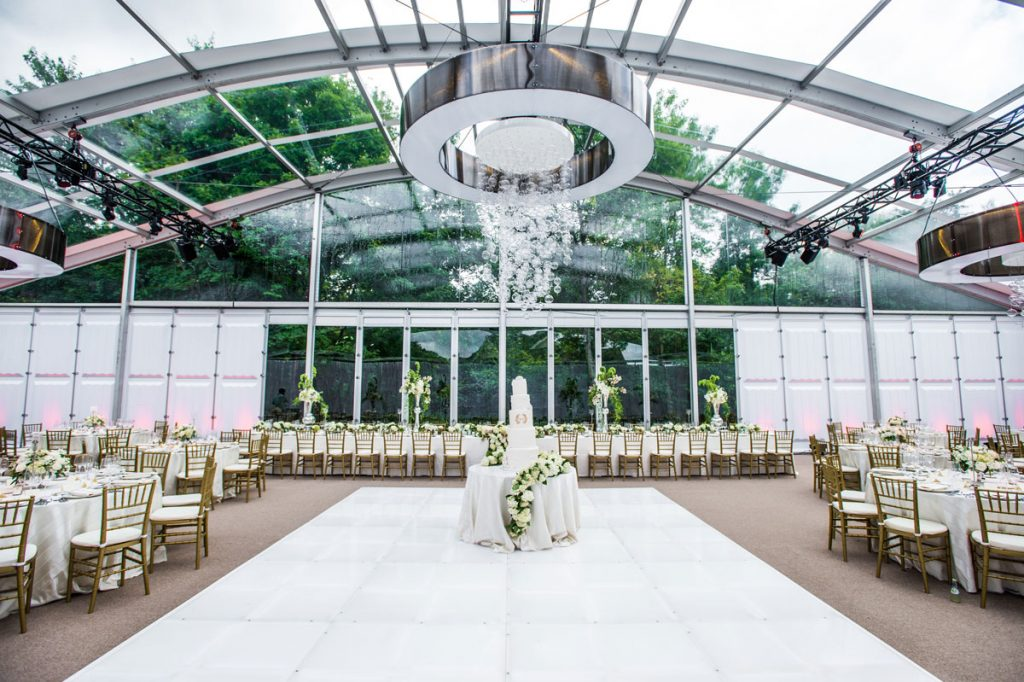 Harvest tables at wedding with tall white ceiling and glass ball chandelier