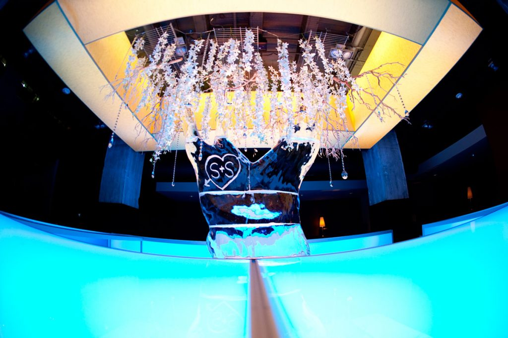 Custom acrylic wedding bar with hanging floral from ceiling and an ice sculpture