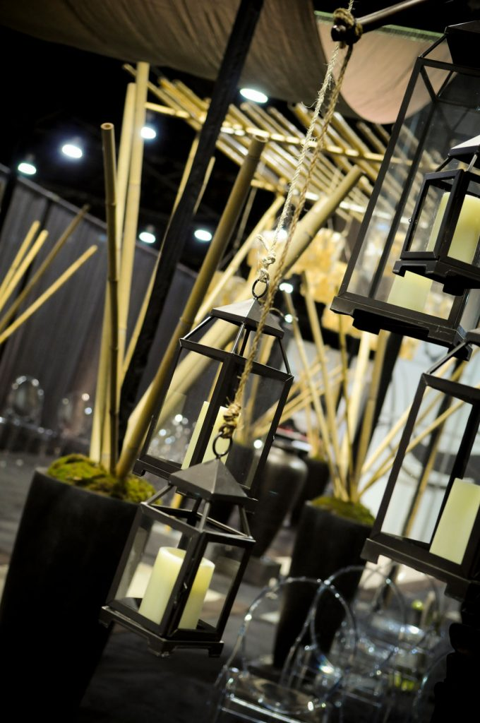 Tall black vases with bamboo and moss inside