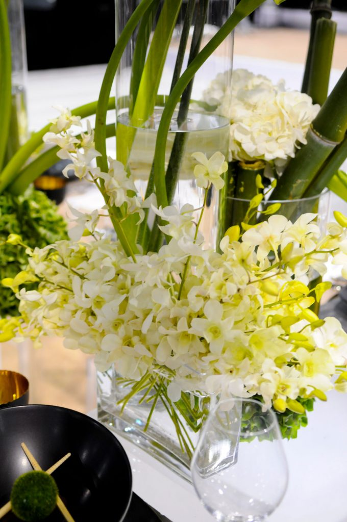 Calla lillies and greens sit in clear vase at wedding table