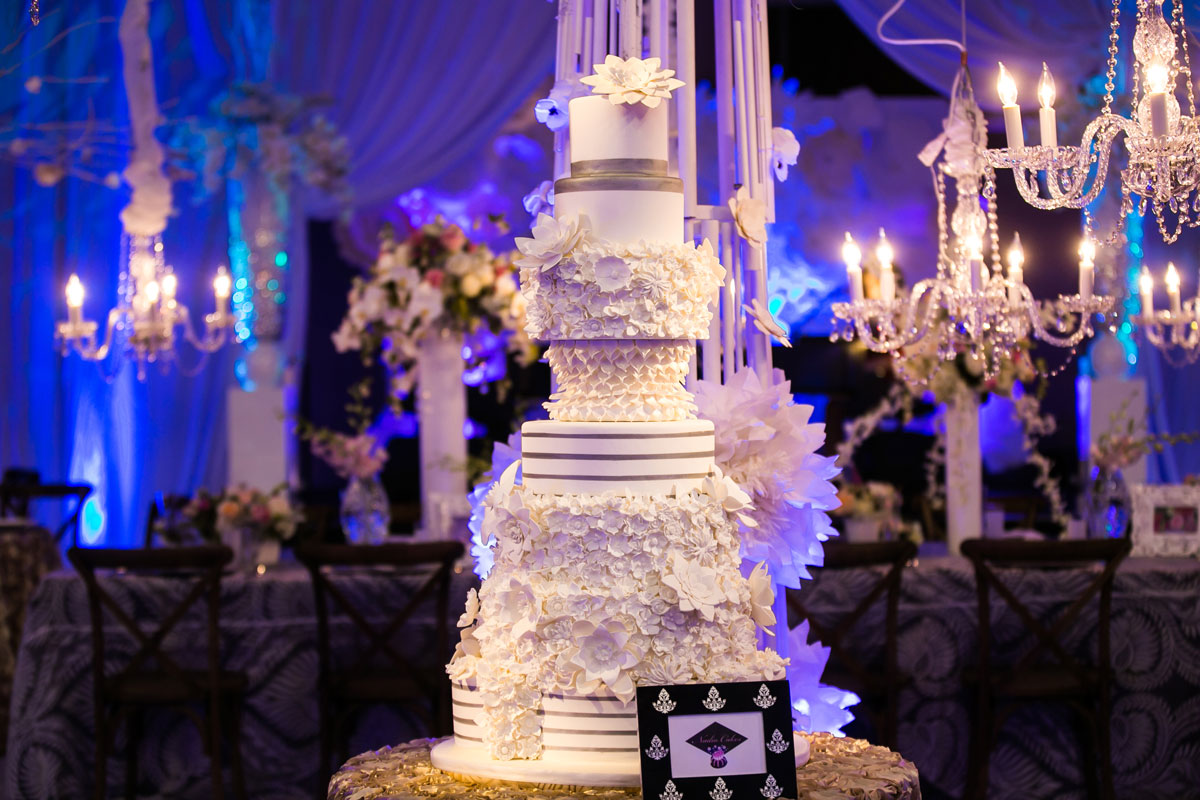 Tall white and silver wedding cake with varying textures and flowers