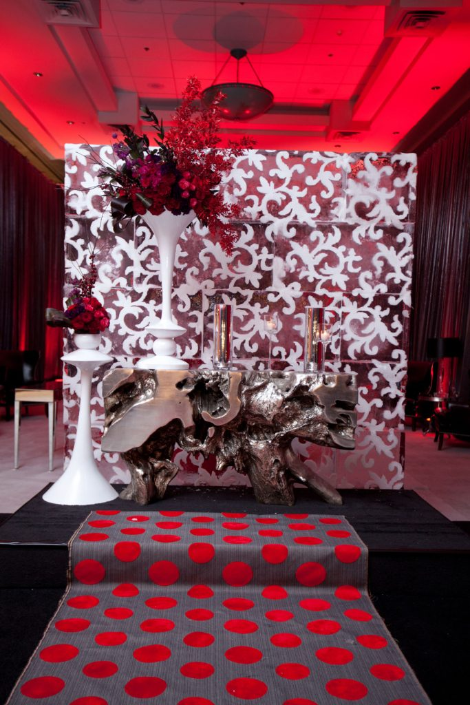 Ice wall sits behind ceremony alter with white trumpet vases