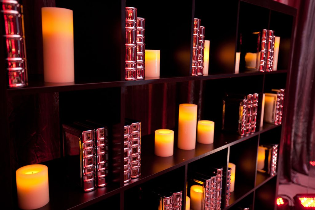 Wedding cocktail lounge with black bookcases, candles, and chrome books