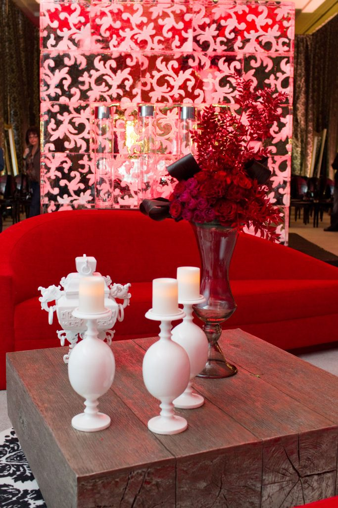 Wedding lounge with red couch, wooden table, and white vases