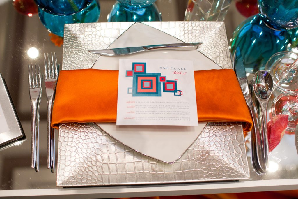 Silver crocodile chargers with square white place and orange napkin