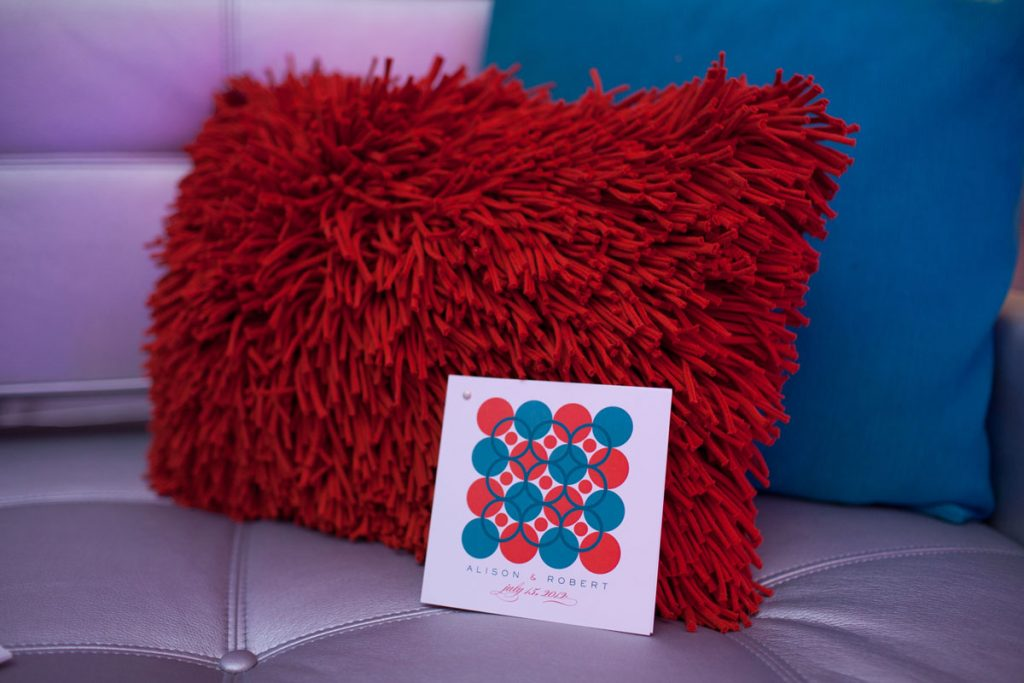 Red shag pillow sits on wedding lounge couch