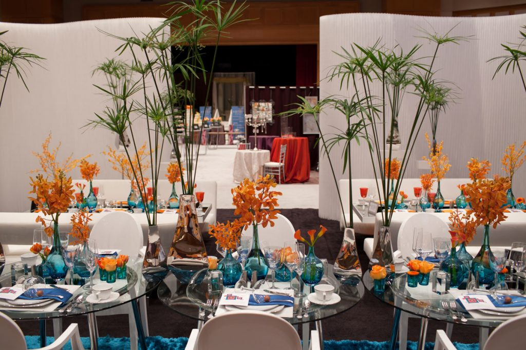 Wedding two-top seating with glass tables and palm fronds
