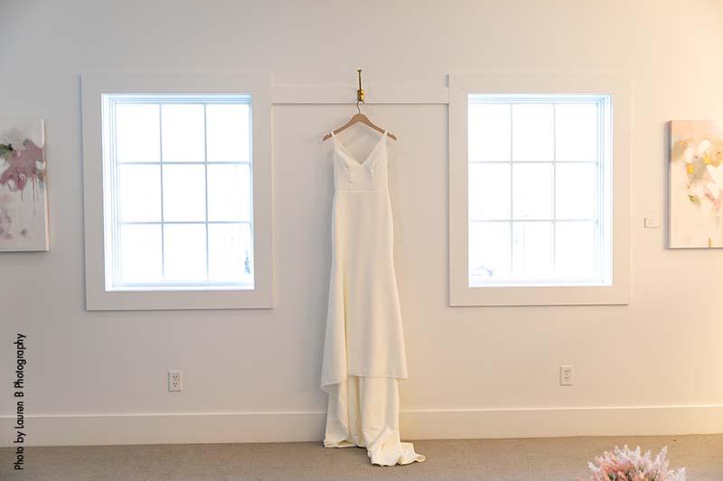 Modern sleek wedding gown hangs from hanger