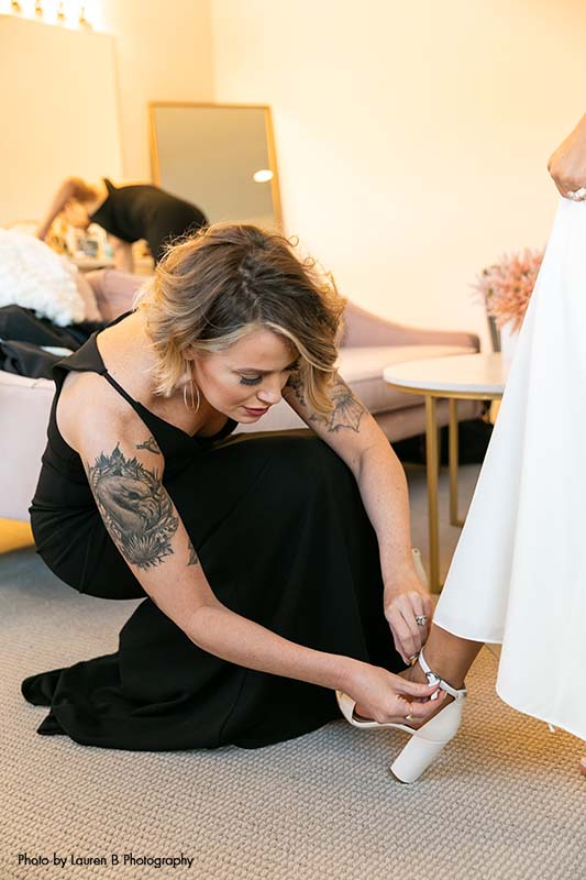 Maid of honor helps bride strap shoe