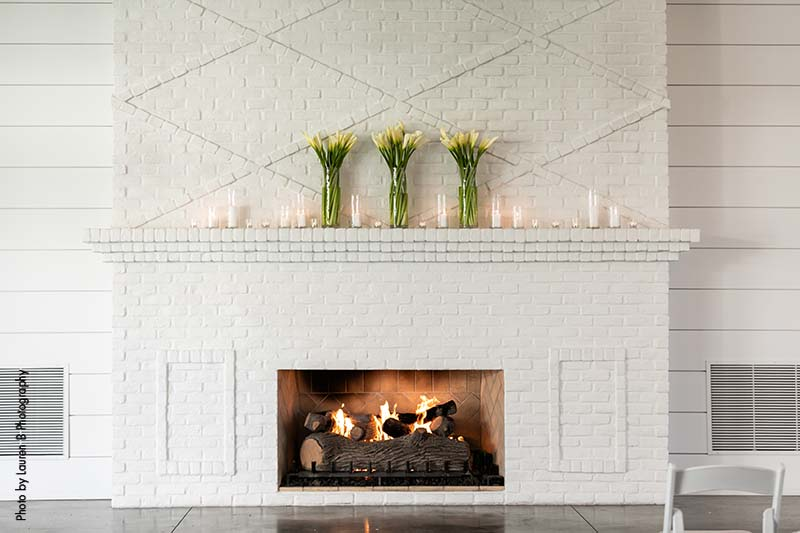 White calla lilies in hurricane vase sit on top of white fireplace