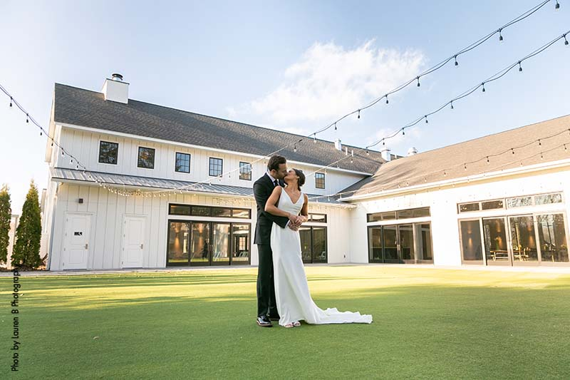 Bride and groom stand in courtyard