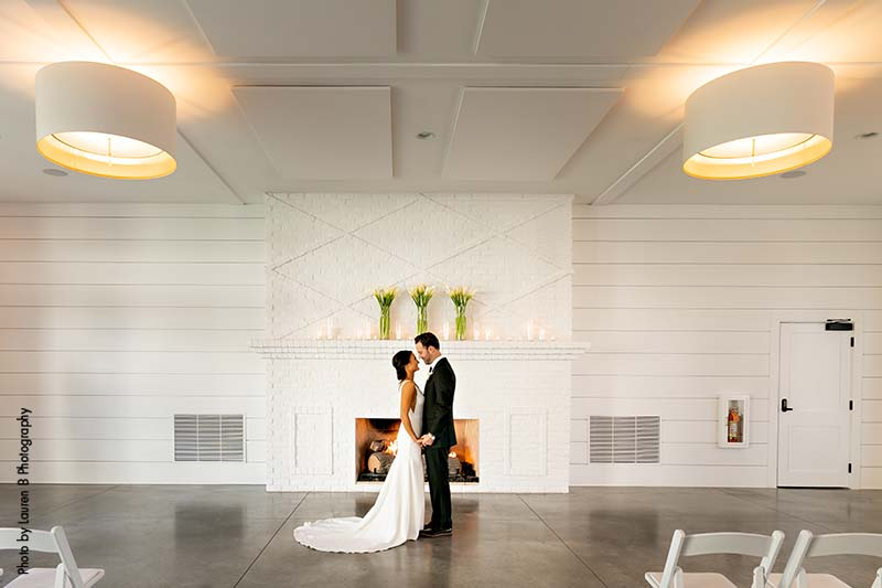 Bride and groom stand in front of all white fireplace