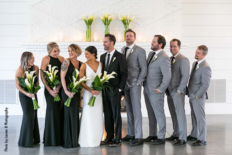 Bridesmaids in black dresses and groomsmen in gray suits