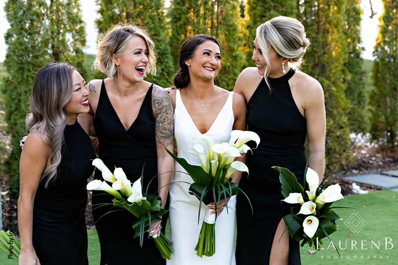 Bride stands with bridesmaids with modern black dresses