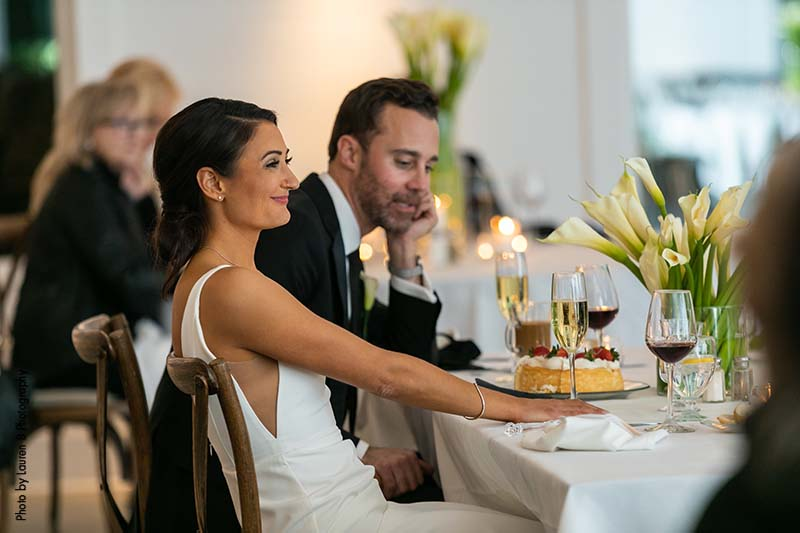 Bride and groom sit at head table at modern wedding in Minneapolis