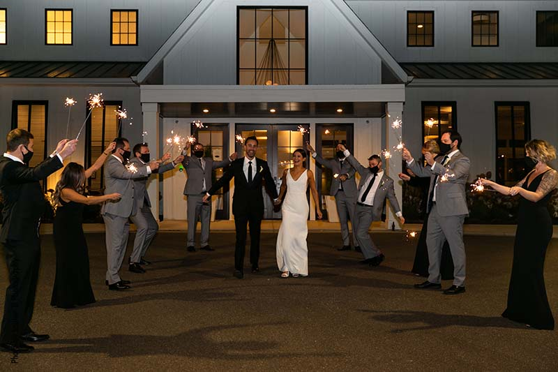 Bride and groom exit wedding as wedding party lights sparklers