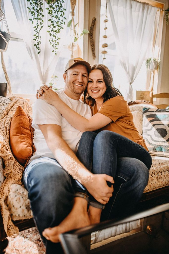 Couple sits on couch for Minneapolis at-home engagement photoshoot by Winsome Photography