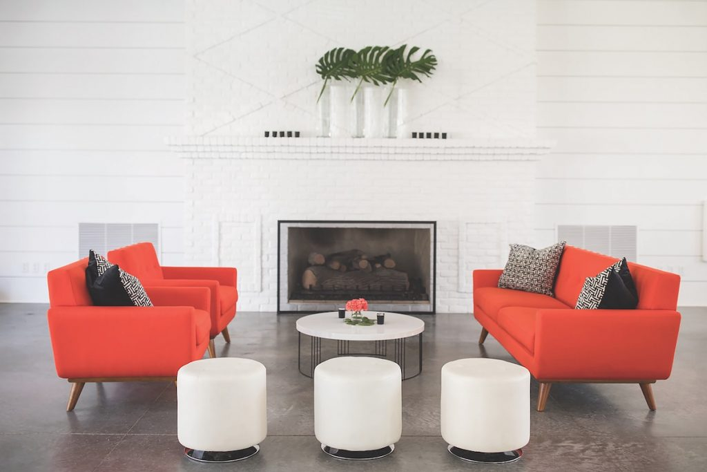 Coral mid-century sofas with white ottomans as wedding lounge space