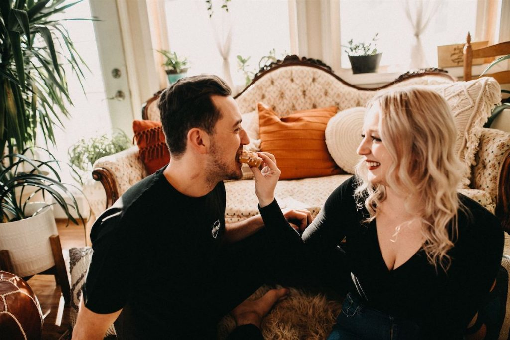 Woman feeds man donut at engagement session