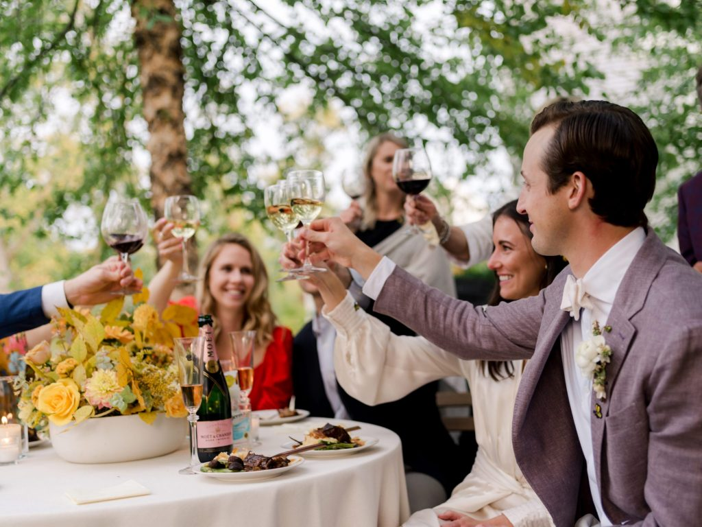 Group at wedding has a toast by Liz Banfield Photography