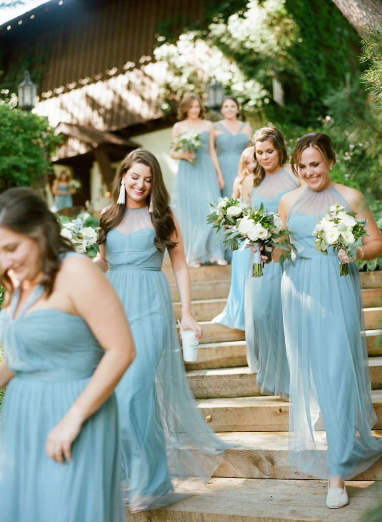 Bridesmaids wearing full length blue gowns by Bella Bridesmaids for outdoor country wedding. Florals by Jackson Durham.